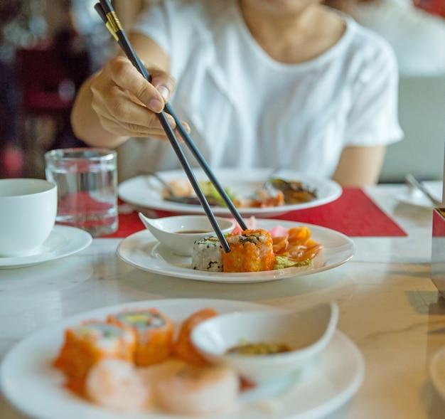 Comendo shushi com pauzinhos, foco seletivo