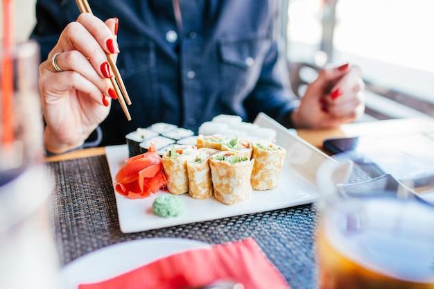 Comendo sushi. close-up da mulher que come o sushi com os pauzinhos no restaurante. o rosto não está visível