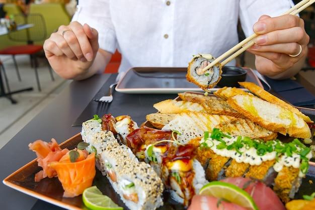 Comendo sushi com pauzinhos em restaurante de sushi