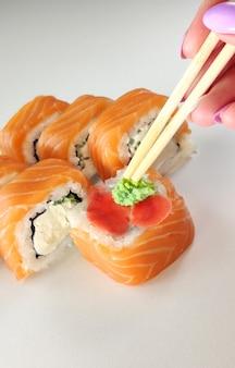 Comendo sushi com pauzinhos. rolo de sushi comida japonesa