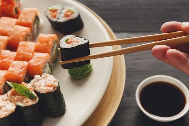 Comendo sushi e pãezinhos em restaurante japonês