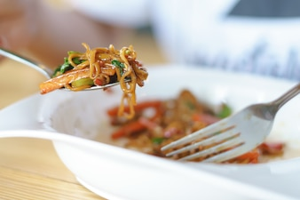 Comendo um macarrão instantâneo frito mexido com vegetais mistos e ingredientes picantes e muito quentes