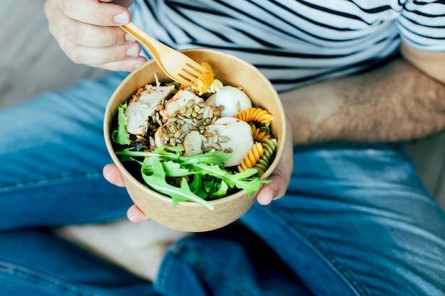 Comendo uma tigela de almoço saudável. frango, macarrão fusilli, alcaparras, mistura de verduras, legumes e sementes de girassol