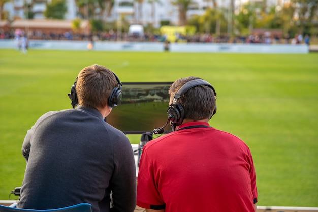 Comentaristas no jogo de futebol assistindo jogo. transmissão para televisão e rádio
