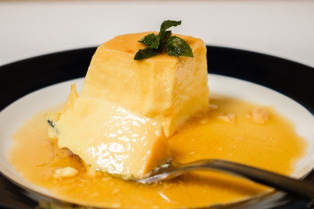 Comer a deliciosa sobremesa típica argentina e sul-americana chamada flan com caramelo. a mão do comensal é observada. conceito de alimentação natural e saudável.