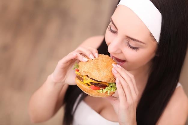 Comer insalubre conceito de junk food. retrato, de, elegante, mulher jovem, comer, hambúrguer