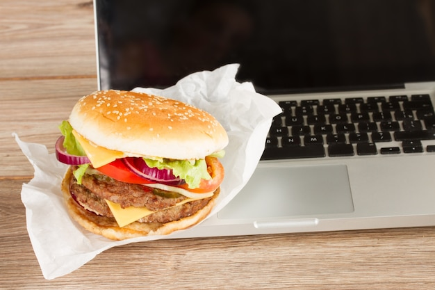 Comer no local de trabalho fast food perto do conceito de laptop