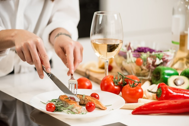 Comer peixe fresco cozido em um prato com legumes e um copo de vinho branco