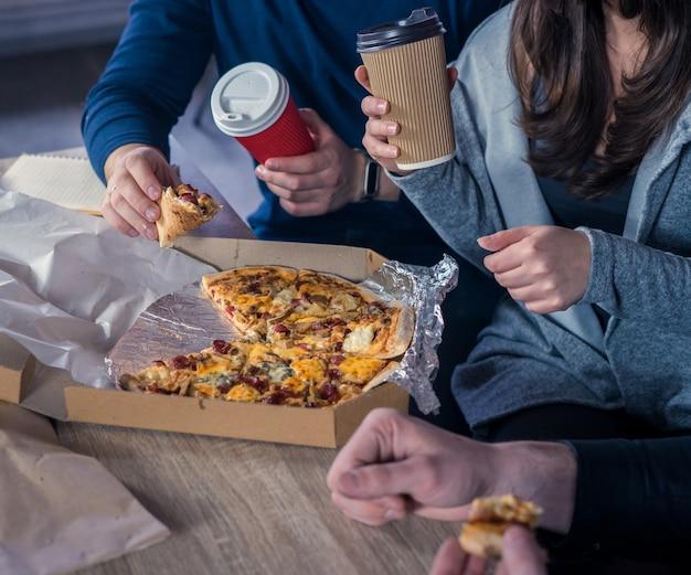 Comer pizza juntos no escritório entrega de comida conceito de amizade