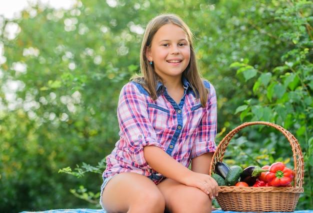 Comer saudável. garoto recolhendo fundo de natureza de vegetais. estilo de vida saudável. conceito de colheita de verão. conceito de comida caseira saudável. menina bonita criança sorridente vivendo uma vida saudável. colheita orgânica.