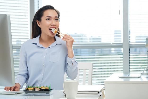 Comer sushi no local de trabalho