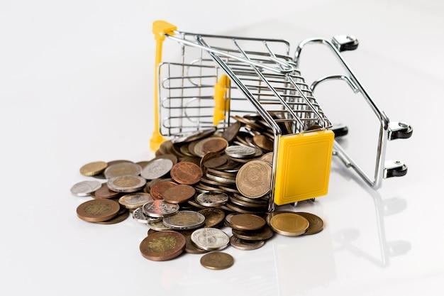 Comercial e financeiro, conceito de compras com carrinho de compras cheio de moedas múltiplas no fundo branco