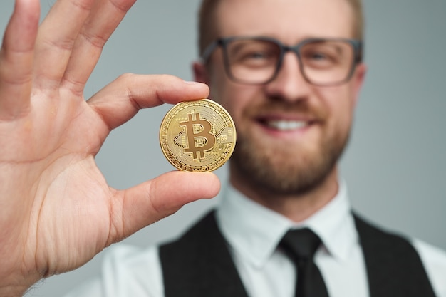 Comerciante barbudo e alegre demonstrando a moeda bitcoin dourada para a câmera enquanto representa o conceito de investimento em criptomoeda