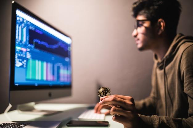 Comerciante de bitcoin indiano, verificando o conceito de análise de dados de negociação de ações, trabalhando no escritório com gráfico financeiro em monitores de computador