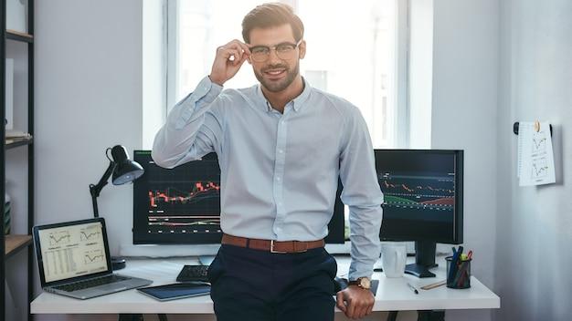 Comerciante de sucesso moderno jovem empresário em roupas formais, ajustando seus óculos e olhando para