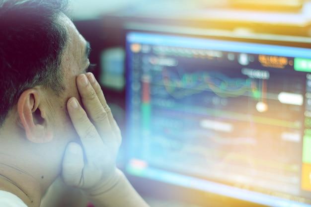 Comerciante está olhando para gráficos financeiros no monitor do computador
