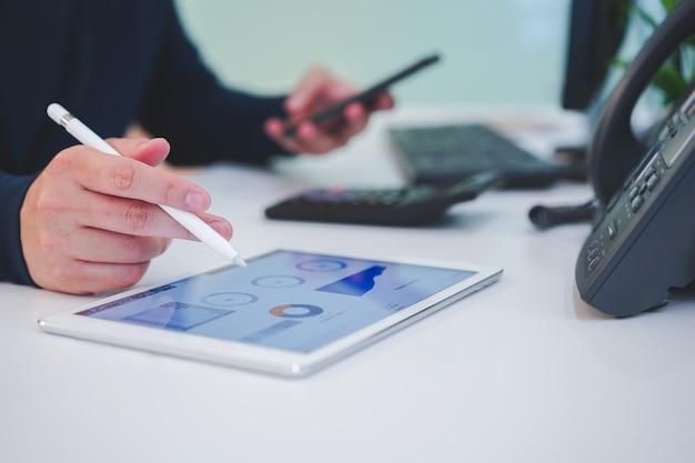 Comerciante homem mão no tablet com painel de estoque gráfico e segurando o smartphone para verificar notícias na mesa