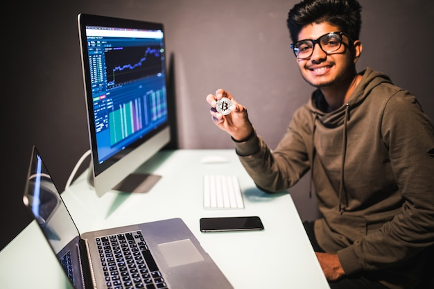 Comerciante indiano com bitcoin, verificando o conceito de análise de dados de negociação de ações trabalhando no escritório com gráfico financeiro em monitores de computador