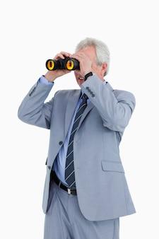 Comerciante maduro olhando através de espião de vidro