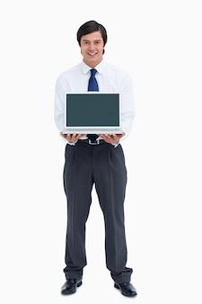 Comerciante sorridente, apresentando a tela do seu laptop