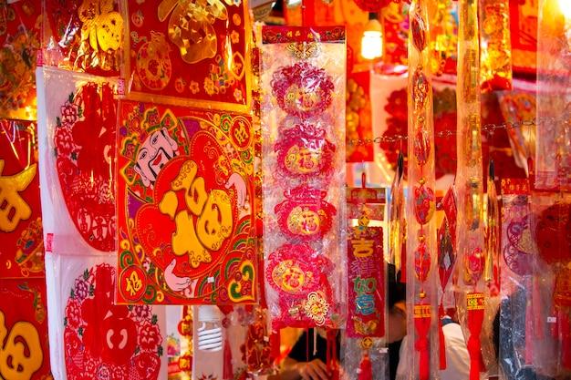 Comerciantes chineses vendem dísticos e ornamentos do festival da primavera durante o festival da primavera. o texto é: a língua da bênção do ano novo chinês
