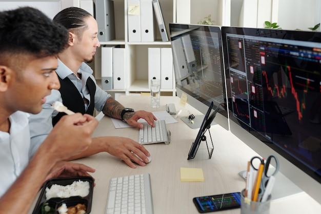 Comerciantes sérios trabalhando na mesa do escritório, analisando as tendências do mercado de ações, comprando e vendendo ações e futuros