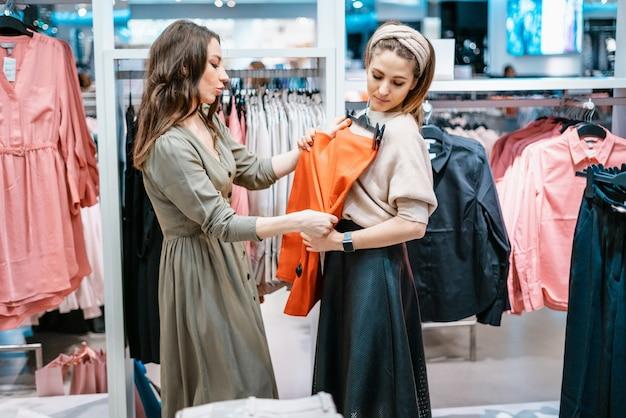 Comércio, compradores. duas lindas meninas fazem compras em um shopping center, vão às compras