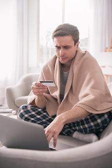 Comércio eletrônico. jovem taciturno sentado em frente ao laptop enquanto digita as informações do cartão