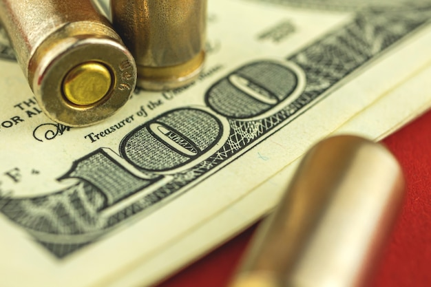 Comércio ilegal de fundo de conceito de munição com balas e dinheiro, foto de close-up de notas de cem dólares dos eua