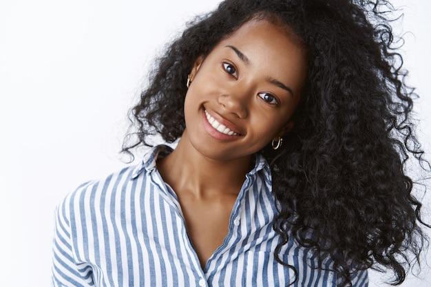 Comestologia, cuidados com a pele, conceito de estilo de vida. mulher jovem e despreocupada de pele escura inclina a cabeça com alegria, sorrindo com os dentes brancos, mostrando um lindo cabelo encaracolado e forte, deliciando-se com a pele perfeita aplicando produtos de spa
