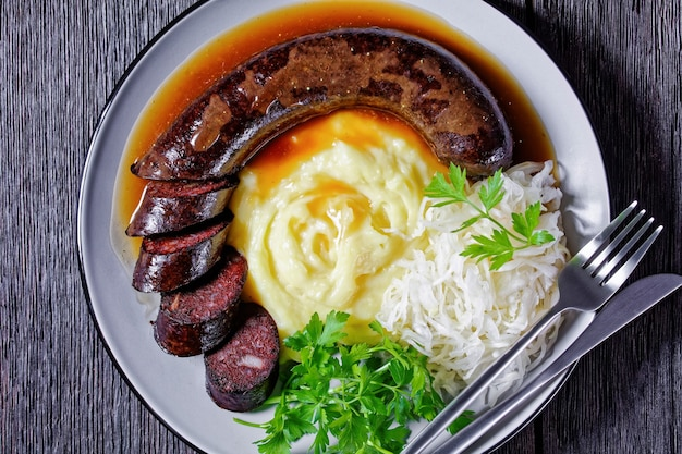 Comida alemã: blutwurst ou linguiça de sangue servida em um prato com chucrute, purê de batata com salsa, mostarda e pimenta em grão em uma mesa de madeira escura, vista de cima, close-up