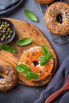 Comida, almoço, brunch, refeição em um prato, conceito de revestimento. bagels com salmão defumado, cream cheese e alcaparras em uma mesa. camada plana, fundo de vista superior.