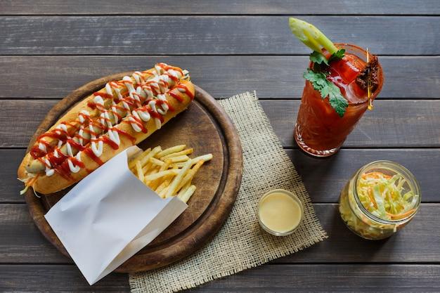 Comida americana - cachorro-quente, suco de tomate com batatas fritas