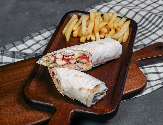 Comida árabe de rua shaurma embrulhada com pão de lavash e batatas fritas.
