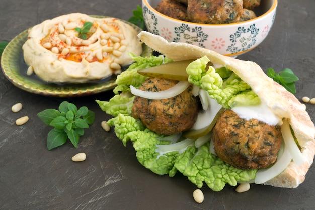 Comida árabe. hummus e falafel em um fundo cinza.