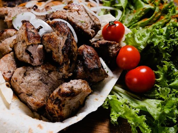 Comida armênia nacional. shashlik carbonizado com fundo de legumes. refeição nutricional e substancial