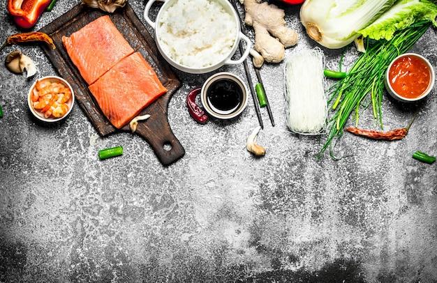 Comida asiática. arroz cozido com um pedaço de salmão e uma variedade de ingredientes. sobre fundo rústico. comida de mesa japonesa.