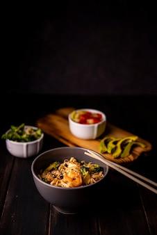 Comida asiática com abacate e pauzinhos
