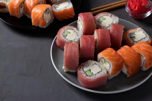 Comida asiática com conjunto de sushi de salmão, atum e enguia com queijo da filadélfia em um fundo escuro. fechar-se