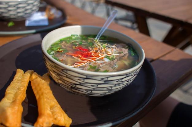 Comida asiática em um prato, sopa de macarrão de arroz, comida de rua no café