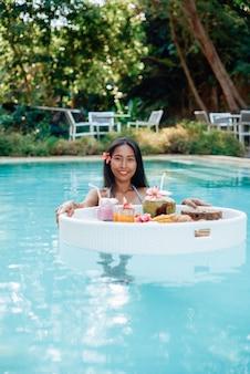 Comida asiática fresca e fresca na mesa flutuante. mulher asiática sedutora e alegre com pele bronzeada nada na piscina com mesa flutuante e olha para a câmera.