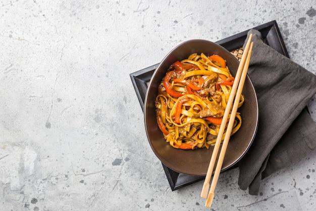 Comida asiática, macarrão udon frito com carne e vegetais em uma tigela em uma superfície de pedra cinza, vista de cima