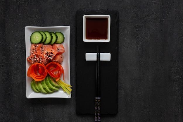 Comida asiática na moda, tigela de sushi poke com pepino, salmão, cenoura, abacate, sementes de gergelim
