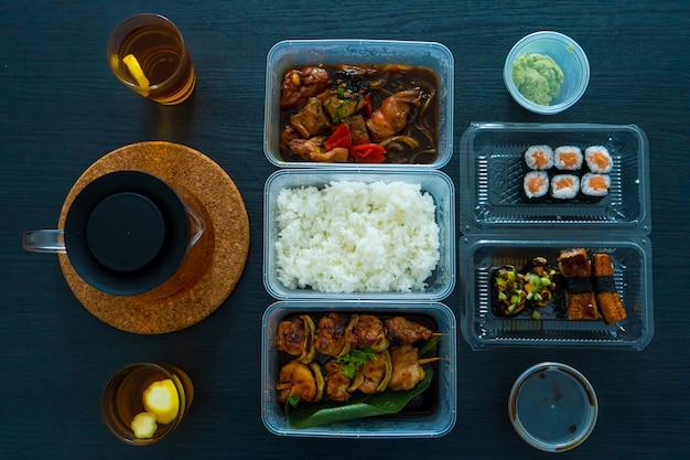 Comida asiática, sushi, pãezinhos, espetos de arroz e frango. comida em pratos descartáveis. encomenda comida asiática em casa