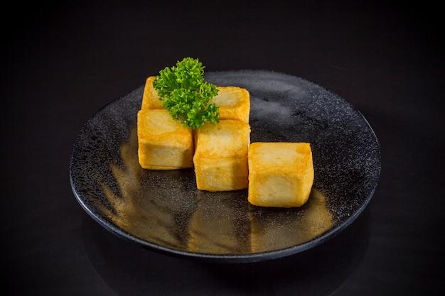 Comida asiática, tofu de peixe frito no fundo preto, comida tradicional japonesa