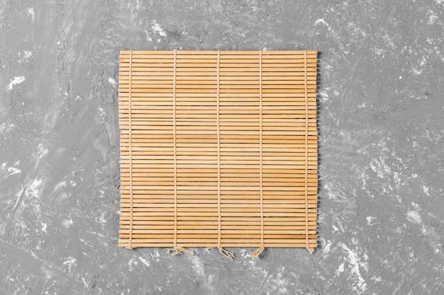 Comida asiática vazia. esteira de bambu marrom na vista superior do plano de fundo de madeira com copyspace plano leigos