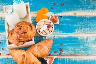 Comida assada com garrafas de leite; flocos de milho; figo e damascos secos sobre prancha de madeira azul