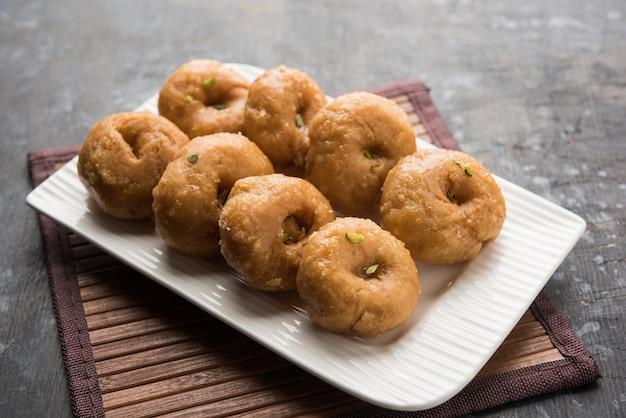 Comida balushahi doce servida em prato branco ou dourado sobre fundo sombrio