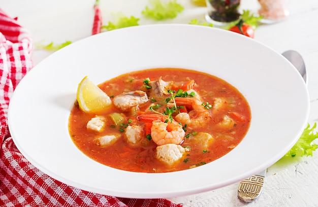 Comida brasileira: moqueca capixaba de peixe e pimentão em molho de coco picante em um prato sobre uma mesa de madeira branca. caldeirada de peixe brasileira.