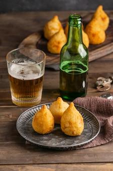 Comida brasileira no prato e copo de cerveja em ângulo alto